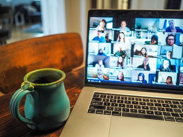 Mug next to laptop with video meeting on screen